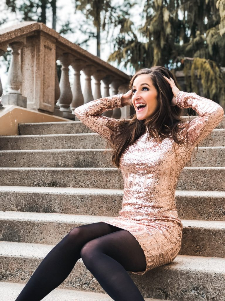 A woman in a glam party dress laughing outside on stone steps