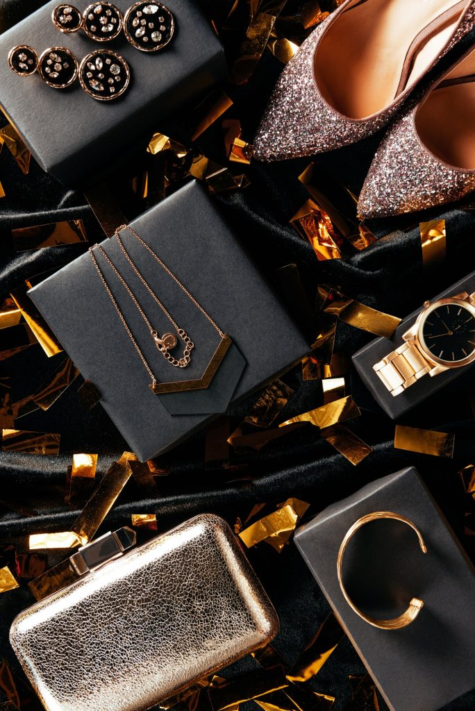 flat lay with feminine shoes, purse and jewelry on black background with golden confetti