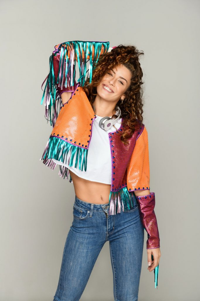 Smiling trendy bohemian woman in multicolored jacket