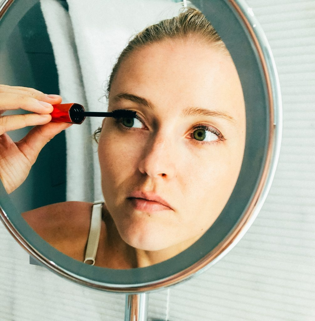 Woman doing her eye make up putting mascara on in the mirror